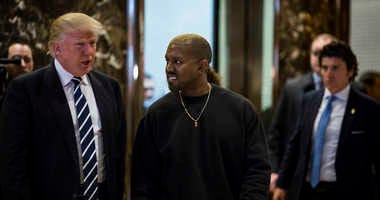 U.S. President-elect Donald J. Trump and Musician Kanye West pose for photographers in the lobby of Trump Tower in Manhattan, New York, U.S., on Tuesday, December 13, 2016.