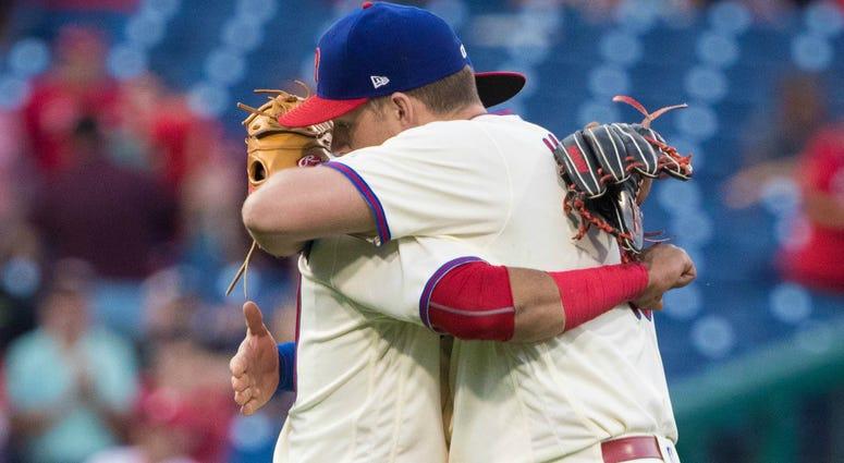 Rhys Hoskins hugs Carlos Santana