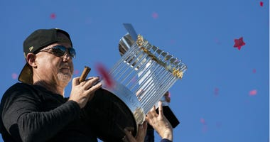 Washington Nationals general manager Mike Rizzo holds the Commissioner's Trophy during a parade to celebrate the World Series.