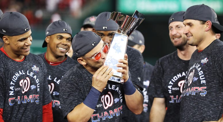 Gerardo Parra celebrates with the trophy after Nationals win Game 4 of the NLCS.