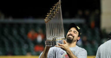 Nationals' Anthony Rendon hoists the Commissioners Trophy after winning World Series.
