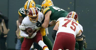 Washington Redskins QB Dwayne Haskins is sacked by a pair of Green Bay Packers.