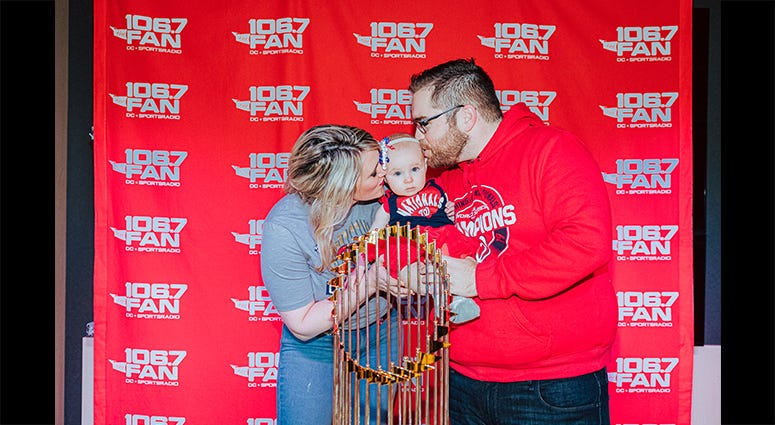 106.7 The Fan host Grant Paulsen and family pose with the World Series trophy