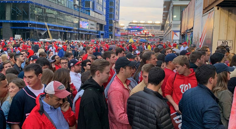 Baseball fans line Half Street before Game 3 of the World Series, Friday night in D.C.