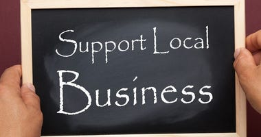 Hands holding blackboard with the text Support Local Business. Business concept.