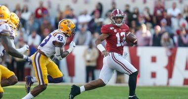 Alabama quarterback Tua Tagovailoa scrambles away from an LSU linebacker.
