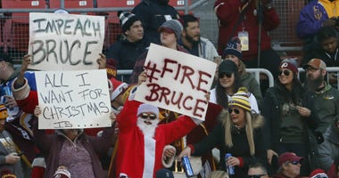 Washington Redskins fans hold signs in the stands against Bruce Allen.
