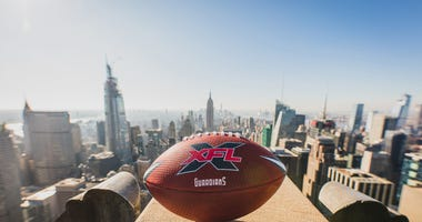 An XFL football sits on a ledge overlooking the New York City skyline.