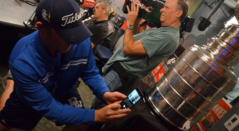 Jason 'Lurch' Bishop snaps a photo of the Stanley Cup