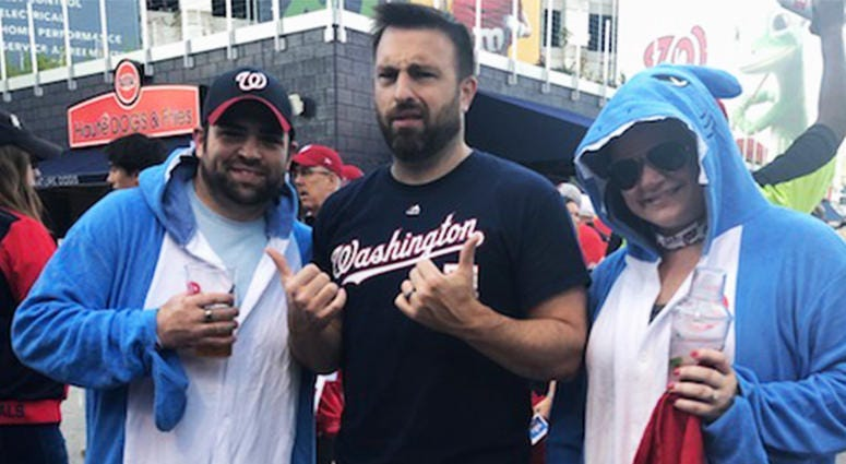 """106.7 The Fan's Danny Rouhier and fans dressed as """"baby shark"""" pose before Game 5 of the World Series at Nationals Park on Sunday, October 27."""