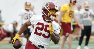 Redskins RB Derrius Guice carries the ball during a practice drill.