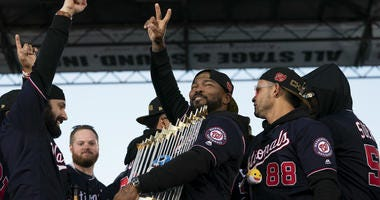 Nationals' Howie Kendrick holds the Commissioner's Trophy during a parade to celebrate the Washington Nationals World Series victory.