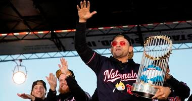 Gerardo Parra of the Washington Nationals holds the Commissioner's Trophy on stage during Nats World Series parade.