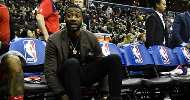 John Wall sits on the Wizards bench during a January game.