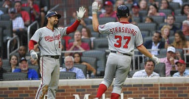 Stephen Strasburg and Anthony Rendon high-five after scoring for the Nationals.