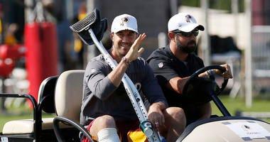 Injured Washington Redskins quarterback Alex Smith waves to fans at training camp.