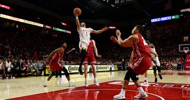 Background: Jan 14, 2019; College Park, MD, USA; Maryland Terrapins guard Anthony Cowan Jr. (1) shoots on the run in-between Wisconsin Badgers defender during the second half at XFINITY Center. Mandatory Credit: Tommy Gilligan