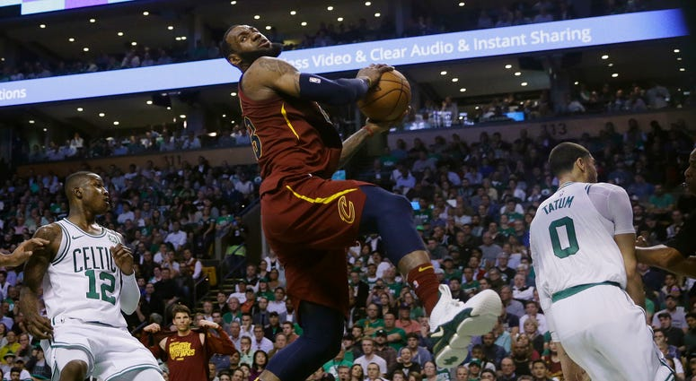 Cavaliers forward LeBron James, center, recoils after colliding with Boston Celtics forward Jayson Tatum, right, in front of Celtics guard Terry Rozier, left, during the first half in Game 2 of the NBA basketball Eastern Conference finals
