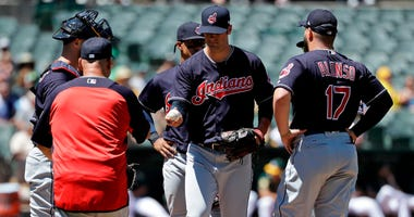 Cleveland Indians starting pitcher Adam Plutko, center, is pulled from the game by manager Terry Francona, left, during the sixth inning of a baseball game against the Oakland Athletics ,Saturday, June 30, 2018, in Oakland, Calif.