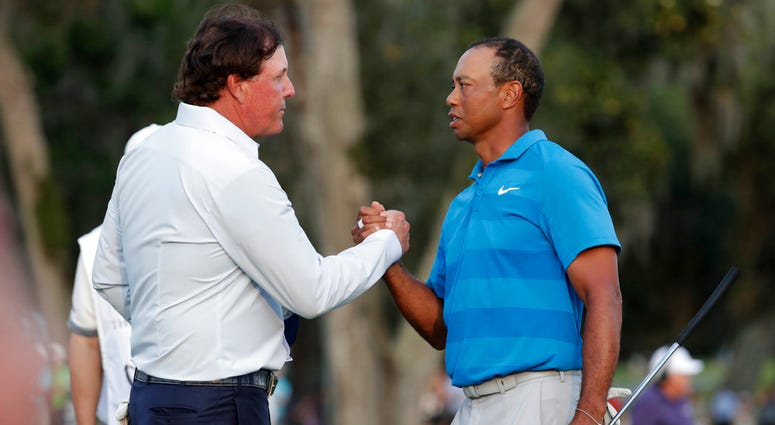Phil Mickelson, left, and Tiger Woods shake hands after the first round of the Players Championship golf tournament, in Ponte Vedra Beach, Fla. The winner-take-all match between Tiger Woods and Phil Mickelson is on. WarnerMedia says it has secured the rig