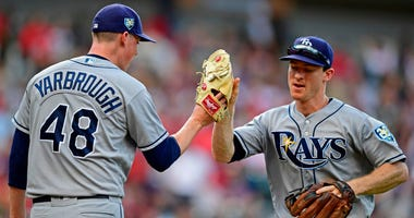 Tampa Bay Rays' Joey Wendle, right, is congratulated by relief pitcher Ryan Yarbrough after throwing out Cleveland Indians' Francisco Lindor in the third inning of a baseball game, Sunday, Sept. 2, 2018, in Cleveland.
