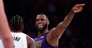 Los Angeles Lakers forward LeBron James, right, gestures to his teammates while being guarded by Portland Trail Blazers forward Al-Farouq Aminu during the second half of an NBA basketball game Wednesday, Nov. 14, 2018, in Los Angeles. The Lakers won 126-1