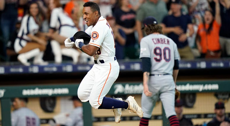 Houston Astros' Tony Kemp, left, celebrates after hitting the game-winning home run as Cleveland Indians relief pitcher Adam Cimber (90) walks to the dugout during the 10th inning of a baseball game Saturday, April 27, 2019, in Houston. The Astros won 4-3