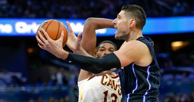 Orlando Magic's Nikola Vucevic, right, goes up for a shot past Cleveland Cavaliers' Tristan Thompson (13) during the first half of an NBA basketball game Wednesday, Oct. 23, 2019, in Orlando, Fla. (AP Photo/John Raoux)