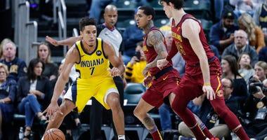 Indiana Pacers guard Malcolm Brogdon (7) drives on Cleveland Cavaliers guard Jordan Clarkson and forward Cedi Osman (16)