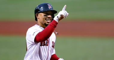 Mookie Betts smiles as he crosses home plate on his solo home run off Oakland Athletics starting pitcher Aaron Brooks in the first inning of a baseball game at Fenway Park in Boston. Betts and the Red Sox agreed Friday, Jan. 10, 2020, to a $27 million con