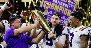 LSU head coach Ed Orgeron, left, and quarterback Joe Burrow, center, hold the trophy beside safety Grant Delpit after a NCAA College Football Playoff national championship game against Clemson, Monday, Jan. 13, 2020, in New Orleans. LSU won 42-25. (AP Pho