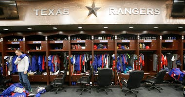 In this Oct. 11, 2016, file photo, Texas Rangers pitcher Sam Dyson, left, packs a bag in the locker room at the baseball park in Arlington, Texas. The NBA, NHL, Major League Baseball and Major League Soccer are closing access to locker rooms and clubhouse