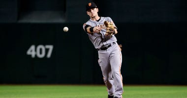 PHOENIX, ARIZONA - AUGUST 15: Scooter Gennett #14 of the San Francisco Giants makes the out at first in the ninth inning of the MLB game against the Arizona Diamondbacks at Chase Field on August 15, 2019 in Phoenix, Arizona. The San Francisco Giants won 7