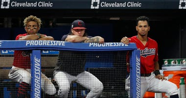 CLEVELAND, OH - SEPTEMBER 21: Francisco Lindor #12, Mike Clevinger #52 and Oscar Mercado #35 of the Cleveland Indians watch from the dugout during the sixth inning against the Philadelphia Phillies at Progressive Field on September 21, 2019 in Cleveland,