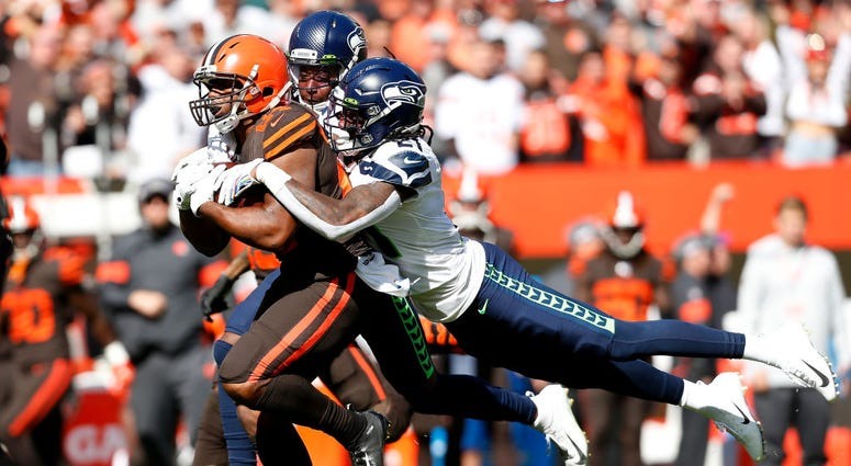 CLEVELAND, OH - OCTOBER 13: Shaquill Griffin #26 of the Seattle Seahawks and Tre Flowers #21 combine to tackle Nick Chubb #24 of the Cleveland Browns during the first quarter at FirstEnergy Stadium on October 13, 2019 in Cleveland, Ohio. (Photo by Kirk Ir