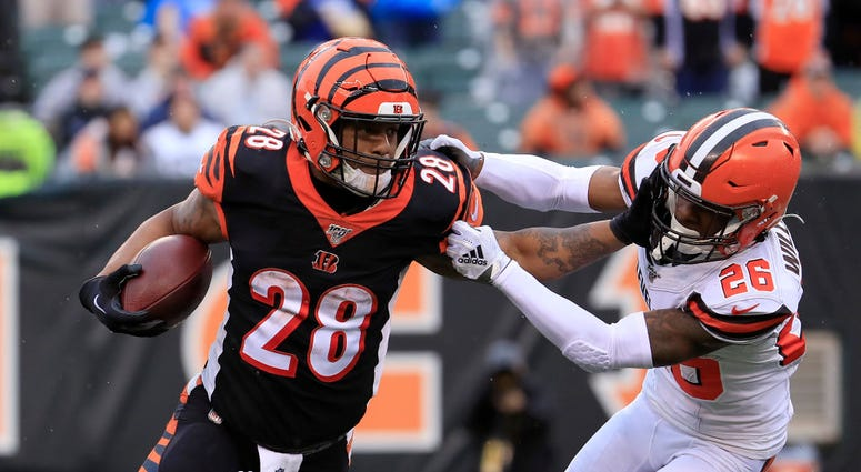 Joe Mixon #28 of the Cincinnati Bengals runs with the ball while defended by Greedy Williams #26 of the Cleveland Browns at Paul Brown Stadium on December 29, 2019 in Cincinnati, Ohio. (Photo by Andy Lyons/Getty Images)