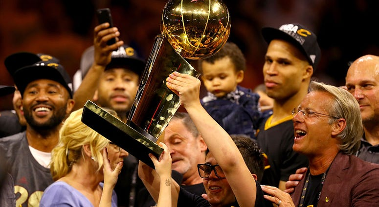 OAKLAND, CA - JUNE 19: Nick Gilbert, son of Cleveland Cavaliers owner Dan Gilbert, holds the Larry O'Brien Championship Trophy after the Cavaliers defeated the Golden State Warriors 93-89 in Game 7 of the 2016 NBA Finals at ORACLE Arena on June 19, 2016 i