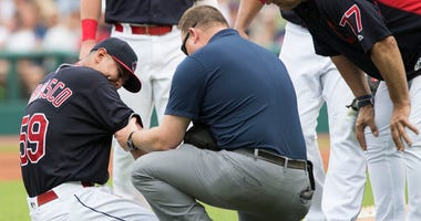 Jun 16, 2018; Cleveland, OH, USA; Cleveland Indians starting pitcher Carlos Carrasco (59) is treated after being hit by a batted ball during the second inning against the Minnesota Twins at Progressive Field.