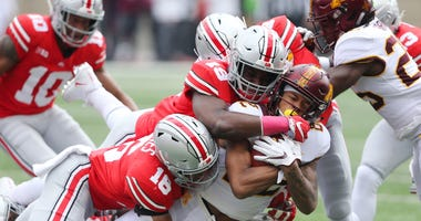 Minnesota Golden Gophers wide receiver Demetrius Douglas (82) is tackled by Ohio State Buckeyes linebacker Dallas Gant (19) and linebacker Keandre Jones (16) during the second quarter at Ohio Stadium.