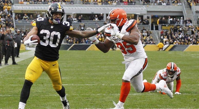 James Conner of the Pittsburgh Steelers stiff-arms Myles Garrett of the Cleveland Browns