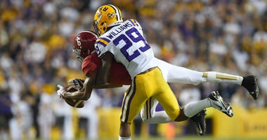 LSU Tigers cornerback Greedy Williams (29) breaks up a pass intended for Alabama Crimson Tide wide receiver DeVonta Smith (6) during the third quarter at Tiger Stadium.