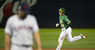 Oakland Athletics third baseman Matt Chapman (right) rounds the bases after hitting the game-winning solo home run against Cleveland Indians pitcher Brad Hand (left) during the 12th inning at Oakland Coliseum.