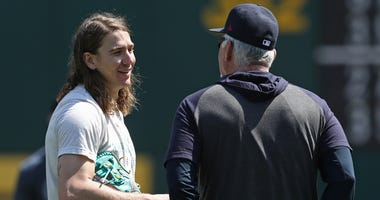 Cleveland Indians pitcher Mike Clevinger (52) talks to pitching coach Carl Willis (51) on the field before the game against the Oakland Athletics at Oakland Coliseum.