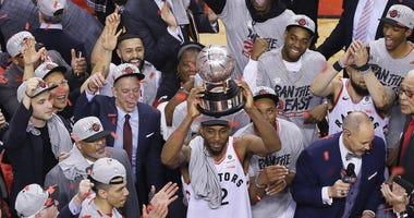 Toronto, Ontario, CAN; Toronto Raptors forward Kawhi Leonard (2) hoist the Eastern Conference trophy after winning game six of the Eastern conference finals