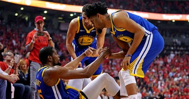 Golden State Warriors forward Kevin Durant (35) is helped up by guard Quinn Cook (4) and guard Klay Thompson (11) after an apparent injury during the second quarter in game five of the 2019 NBA Finals against the Toronto Raptors at Scotiabank Arena.