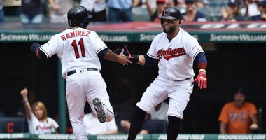 Cleveland Indians third baseman Jose Ramirez (11) and designated hitter Carlos Santana (41) celebrate after scoring during the eighth inning at Progressive Field.