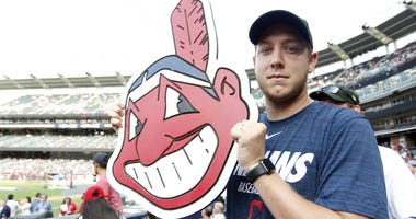 Jul 8, 2019; Cleveland, OH, USA; Cleveland Indians fan Brian Martin stands with a Chief Wahoo poster during workouts before the 2019 MLB All Star Game at Progressive Field. Mandatory Credit: Charles LeClaire-USA TODAY Sports