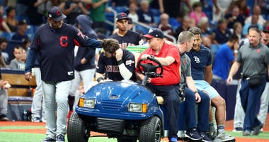 Cleveland Indians right fielder Tyler Naquin (30) is greeted by manager Terry Francona (77) while being carted off the field after an apparent injury at the end of the fifth inning against the Tampa Bay Rays at Tropicana Field.