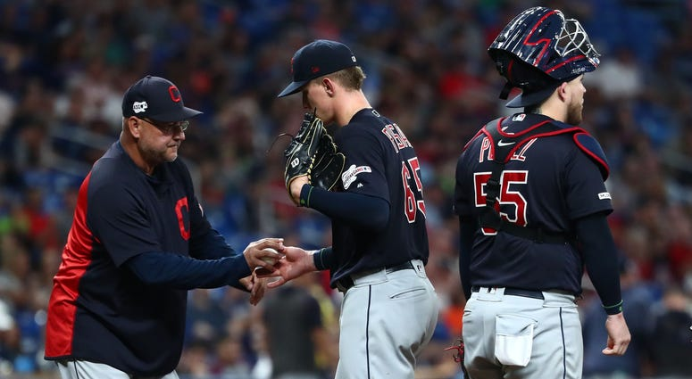 Cleveland Indians manager Terry Francona (77) takes out starting pitcher Zach Plesac (65) during the sixth inning against the Tampa Bay Rays at Tropicana Field.