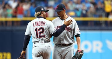 Sep 1, 2019; St. Petersburg, FL, USA; Cleveland Indians pitcher Carlos Carrasco (59) gets a hug from shortstop Francisco Lindor (12) as he comes in to pitch the seventh inning against the Tampa Bay Rays at Tropicana Field. Mandatory Credit: Kim Klement-US